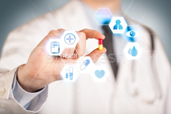 A doctor in white holding a pill Stock photo © ra2studio