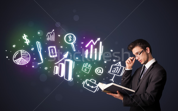 Young guy reading a book with business icons Stock photo © ra2studio