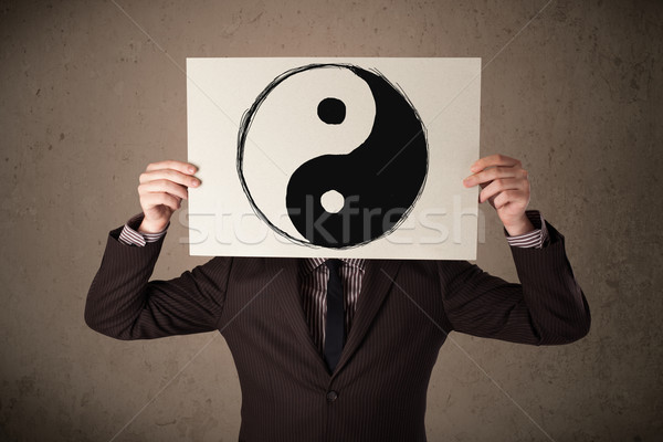 Businessman holding a paper with a yin-yang on it in front of hi Stock photo © ra2studio