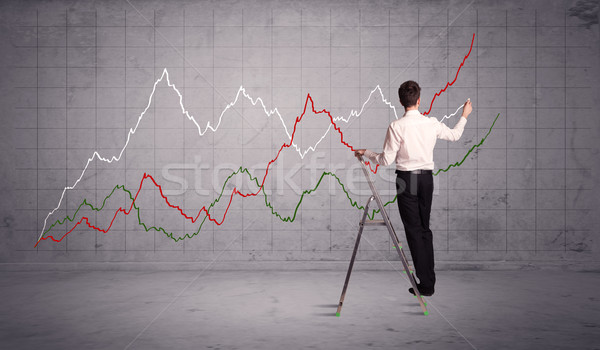 Stock photo: male on ladder drawing chart lines