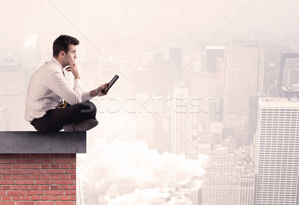 Office worker sitting on rooftop in city Stock photo © ra2studio