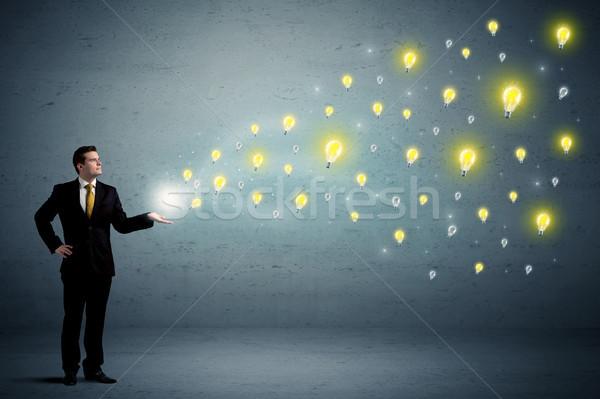 Businessman holding lightbulbs Stock photo © ra2studio