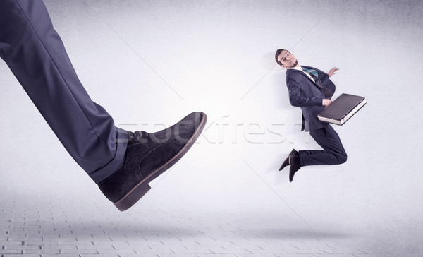 Young worker kicked out by big foot Stock photo © ra2studio