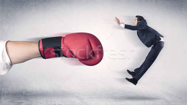 Businessman gets fired by a huge boxing hand Stock photo © ra2studio
