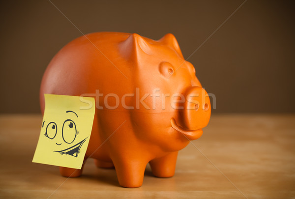 Post-it note with smiley face sticked on a piggy bank Stock photo © ra2studio