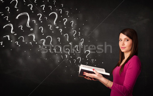 Stock photo: Pretty woman reading a book with question marks coming out from