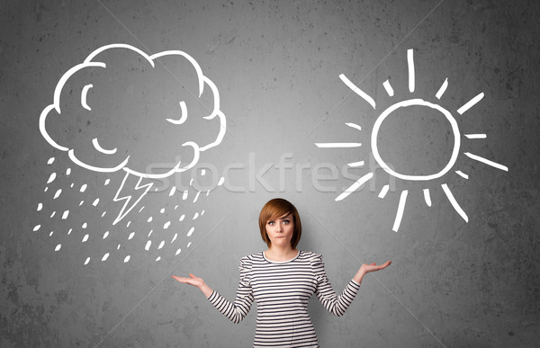 Woman standing between a sun and a rain drawing Stock photo © ra2studio