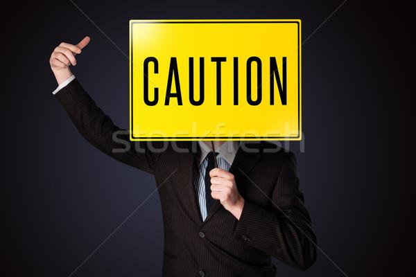 Businessman holding a caution sign Stock photo © ra2studio