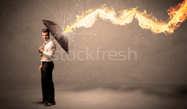 Stock photo: Business man defending himself from a fire arrow with an umbrell