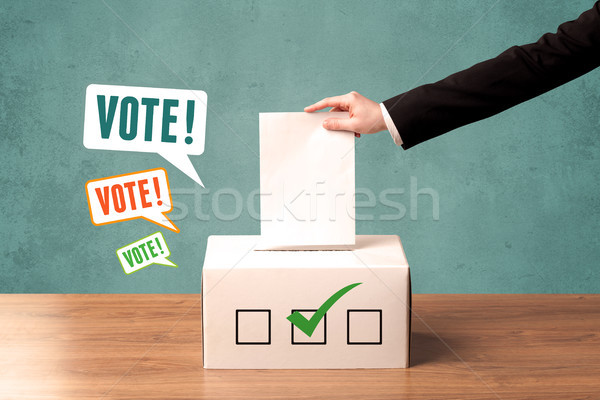placing a voting slip into a ballot box Stock photo © ra2studio