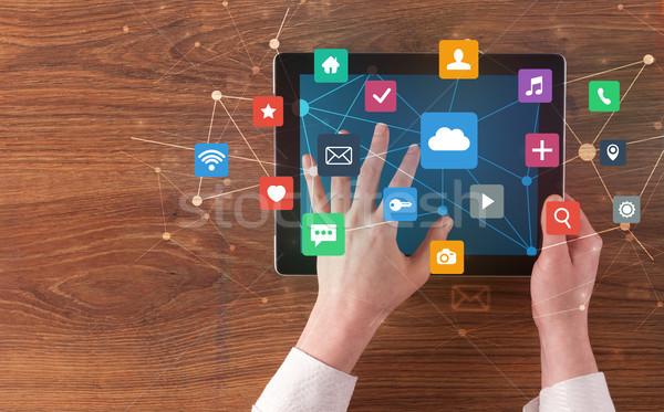 Hand using multitask tablet with application symbols and icons c Stock photo © ra2studio