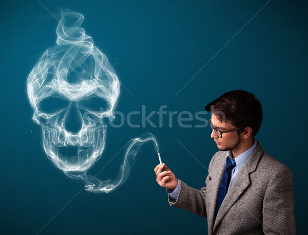 Stock photo: Young man smoking dangerous cigarette with toxic skull smoke
