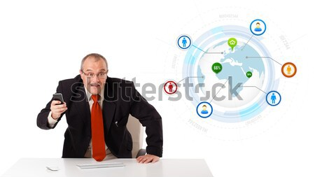 businessman sitting at desk and holding a mobilephone with globe and social icons, isolated on white Stock photo © ra2studio