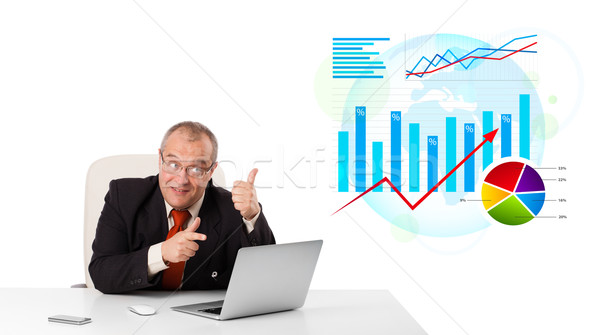 Businessman sitting at desk with laptop and statistics Stock photo © ra2studio