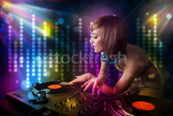 Dj girl playing songs in a disco with light show Stock photo © ra2studio