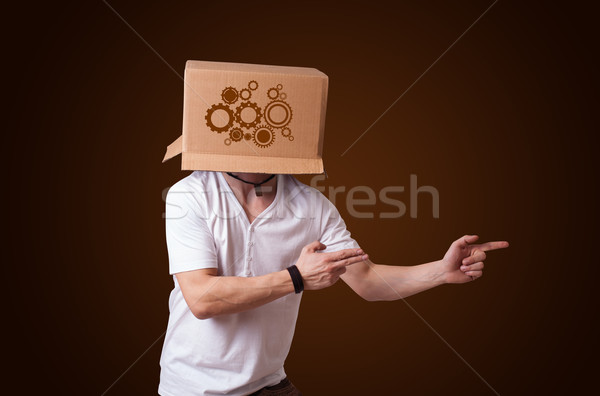Stock photo: Young man gesturing with a cardboard box on his head with spur w