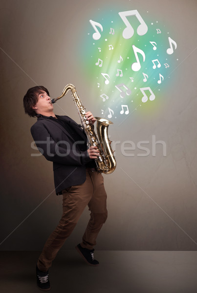 Young musician playing on saxophone while musical notes explodin Stock photo © ra2studio