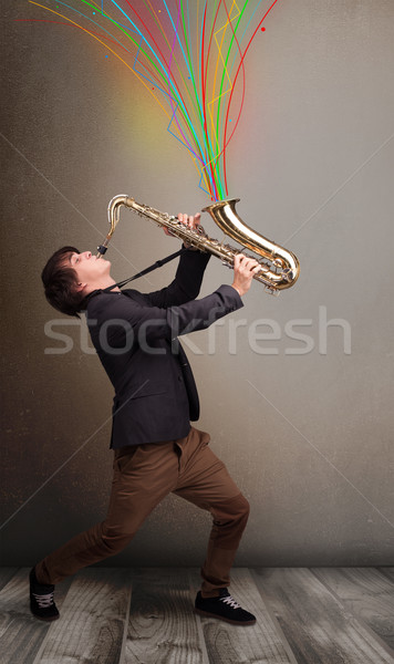 Attractive musician playing on saxophone while colorful abstract Stock photo © ra2studio