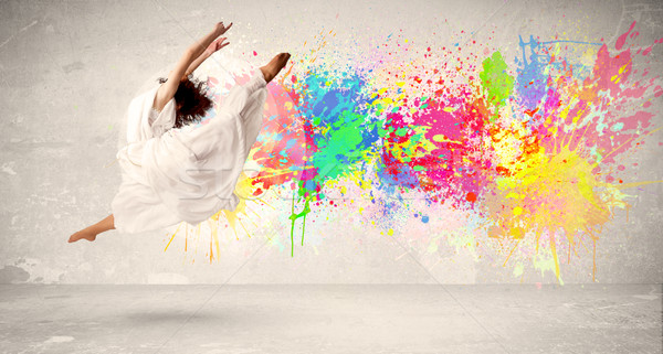 Happy teenager jumping with colorful ink splatter on urban backg Stock photo © ra2studio