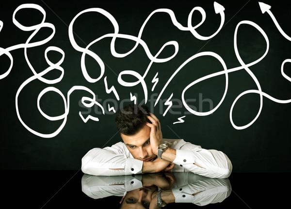Depressed businessman sitting under drawn direction lines Stock photo © ra2studio