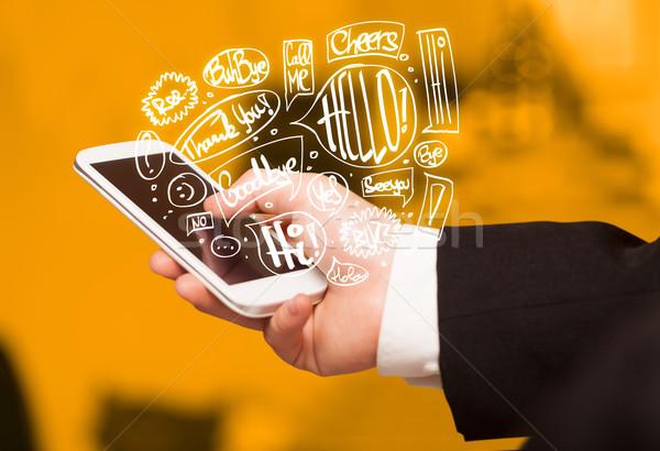 Hand holding phone with hand drawn speech bubbles Stock photo © ra2studio