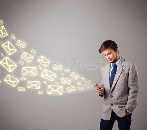 attractive young man holding a phone with message icons Stock photo © ra2studio