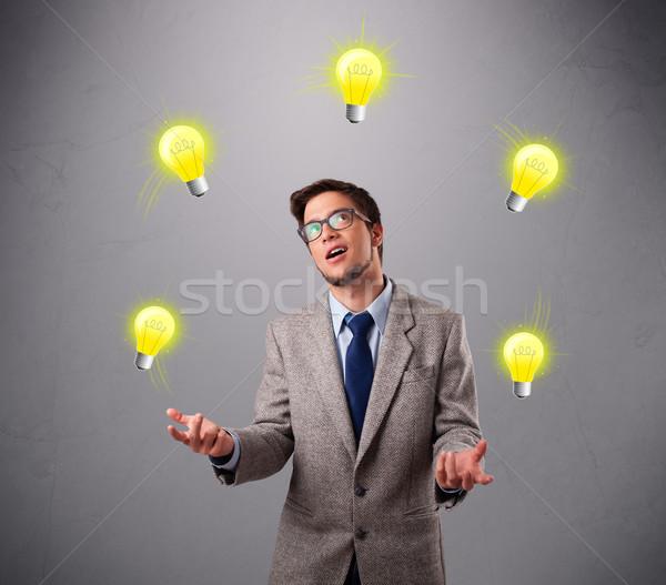Fiatalember áll zsonglőrködés villanykörték vicces kéz Stock fotó © ra2studio
