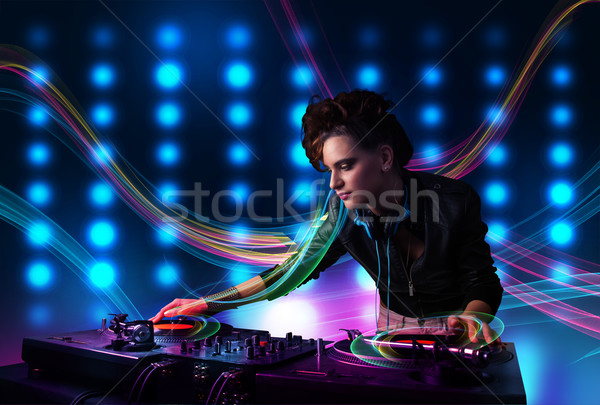 Young Dj girl mixing records with colorful lights Stock photo © ra2studio
