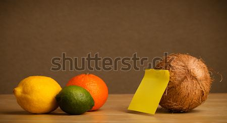 Stock photo: Coconut with post-it note looking at citrus fruits