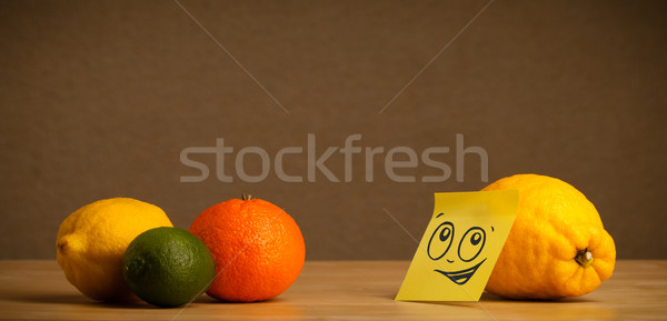 Lemon with post-it note looking at citrus fruits Stock photo © ra2studio