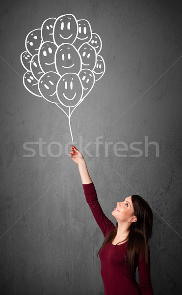 Woman holding a bunch of smiling balloons Stock photo © ra2studio