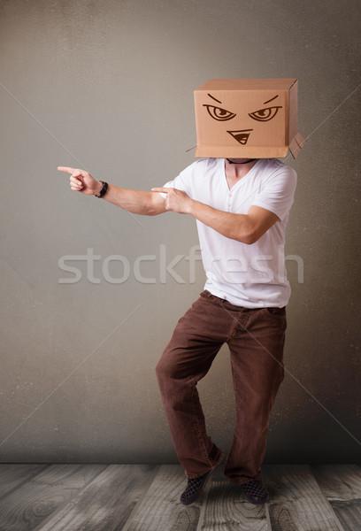 Fiatalember gesztikulál kartondoboz fej gonosz áll Stock fotó © ra2studio