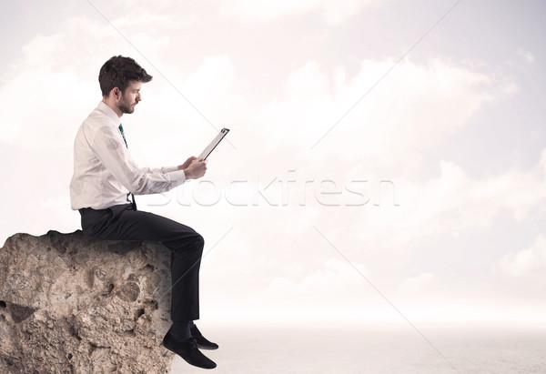 Business man sitting on stone edge Stock photo © ra2studio
