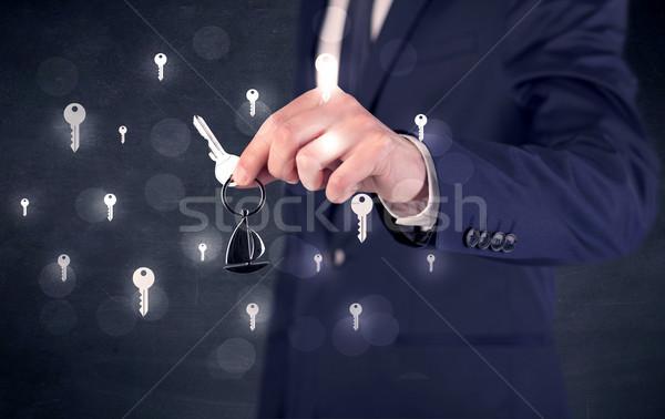 Businessman holding keys with keys around Stock photo © ra2studio