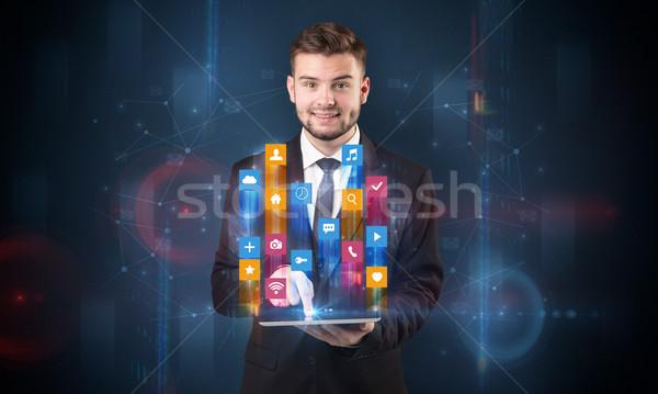 Férfi tart tabletta hologram app ikonok Stock fotó © ra2studio