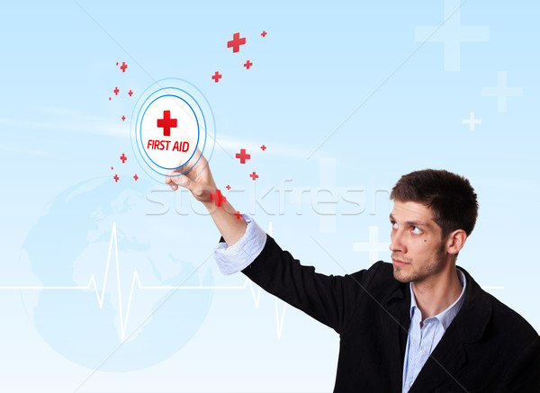 Young doctor pressing first aid button Stock photo © ra2studio