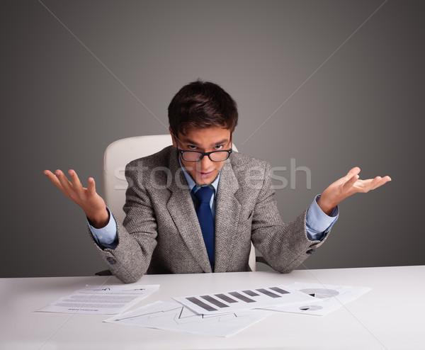 Businessman sitting at desk and doing paperwork Stock photo © ra2studio