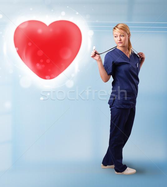Jeunes infirmière guérison rouge coeur joli Photo stock © ra2studio