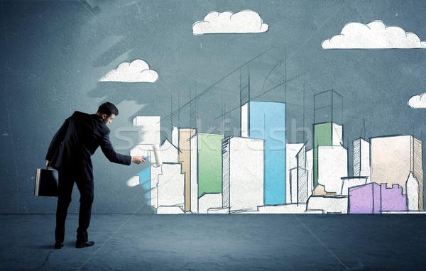 Salesman painting tall buildings on urban wall Stock photo © ra2studio