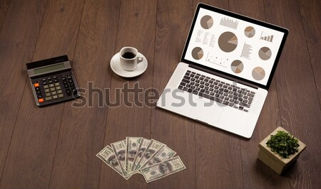 Stock photo: Pie chart graph icons on laptop screen with office accessories