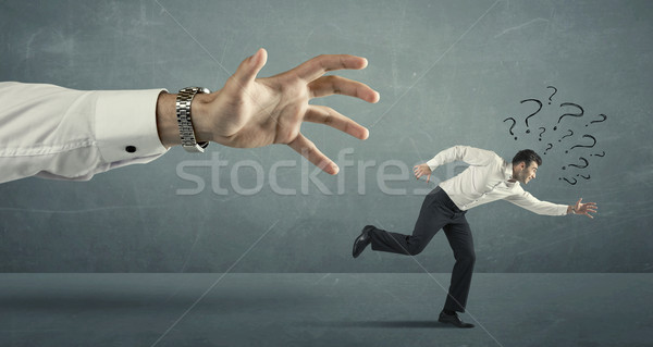 Businessman running away from a big hand Stock photo © ra2studio