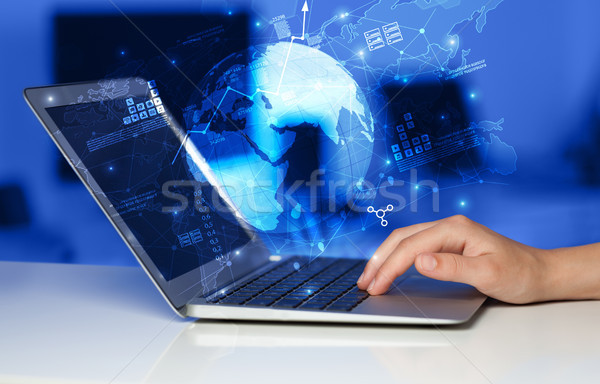 Stock photo: Hand using laptop with worldwide reports links and statistics co