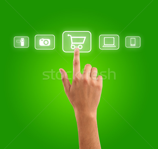 hand choosing shopping cart symbol from media icons on green Stock photo © ra2studio