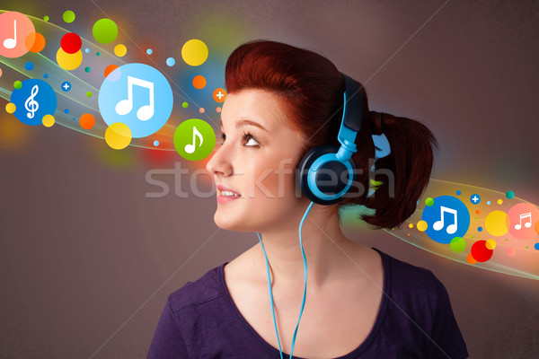 Stock photo: Young woman listening to music with headphones