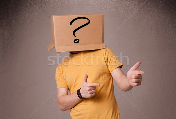 Young man gesturing with a cardboard box on his head with questi Stock photo © ra2studio