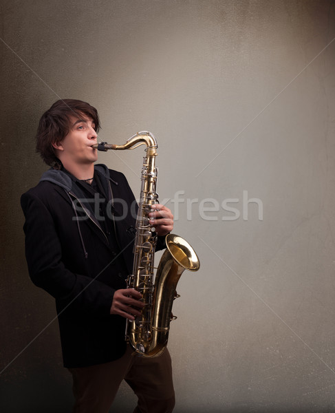 Young musician playing on saxophone Stock photo © ra2studio