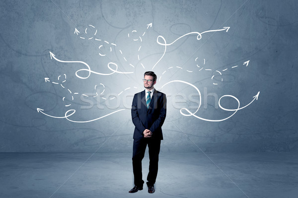 Businessman standing with winding arrows around Stock photo © ra2studio