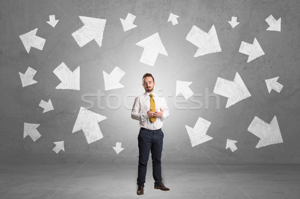 Businessman standing with arrows around Stock photo © ra2studio