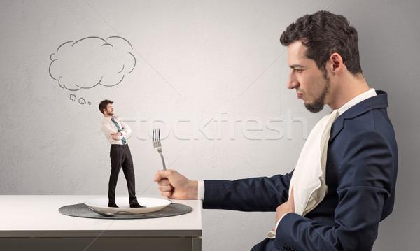Businessman want to eat small man  Stock photo © ra2studio