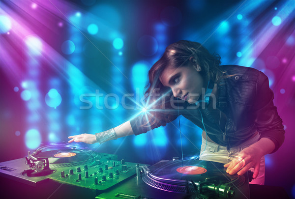 Dj girl mixing music in a club with blue and purple lights Stock photo © ra2studio